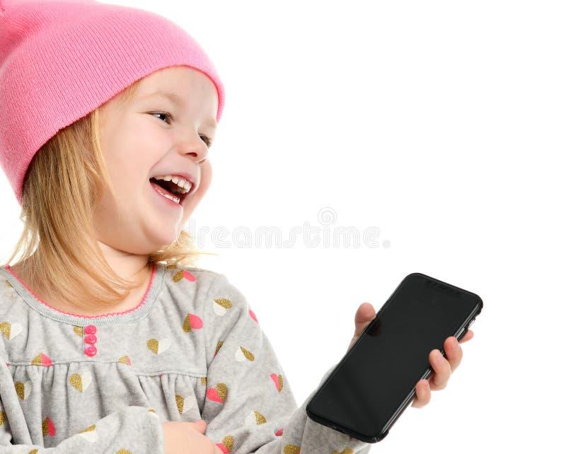Sms texting da leitura da criança da menina no móbil do telefone celular com riso feliz do tela táctil imagens de stock royalty free