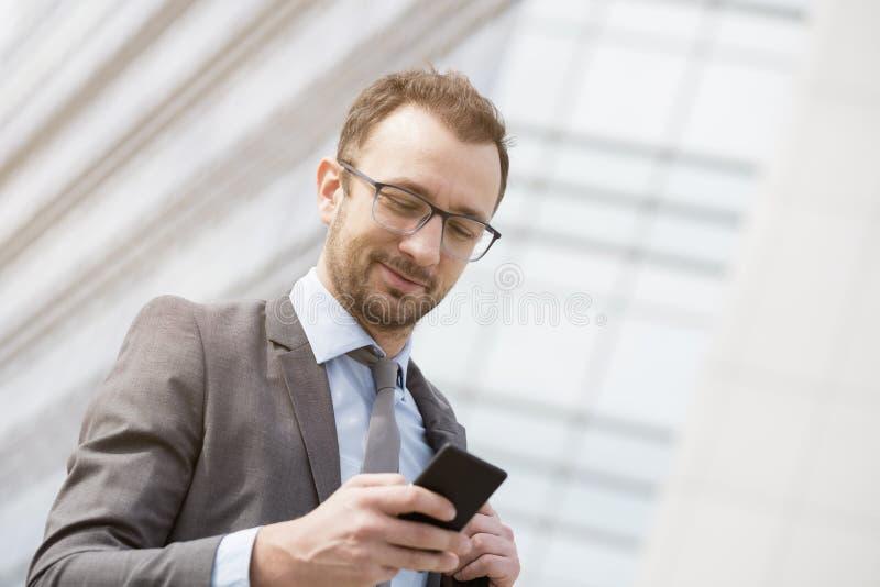 Sms texting do homem de negócios na frente do buil de vidro azul do negócio imagens de stock