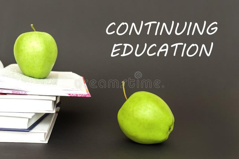 Smsa att fortsätta utbildning, två gröna äpplen, öppna böcker med begrepp royaltyfri foto