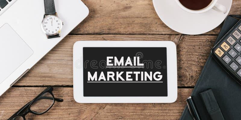 Smsa emailmarknadsföringen på skärmen av tabelldatoren på kontorsskrivbordet royaltyfria foton