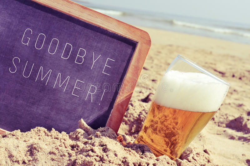 Smsa farvälsommar i en svart tavla och ett exponeringsglas av öl på bet royaltyfri foto