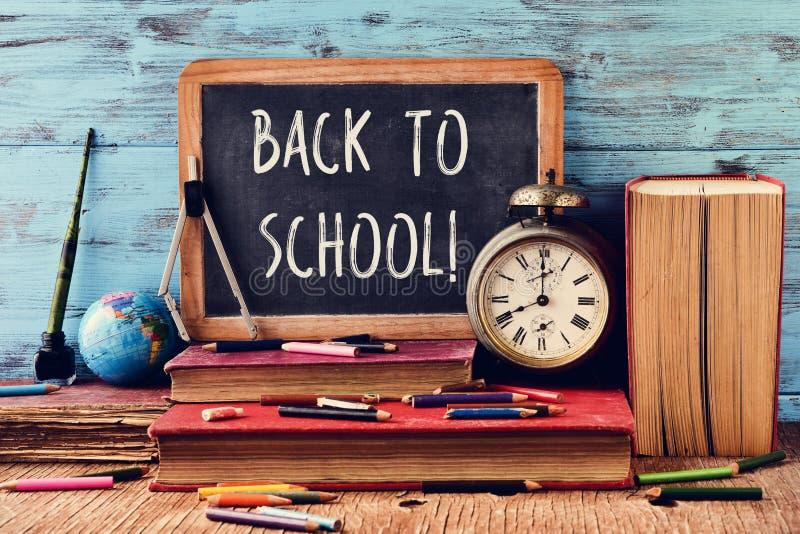 Smsa tillbaka till skolan som är skriftlig på en svart tavla royaltyfria foton