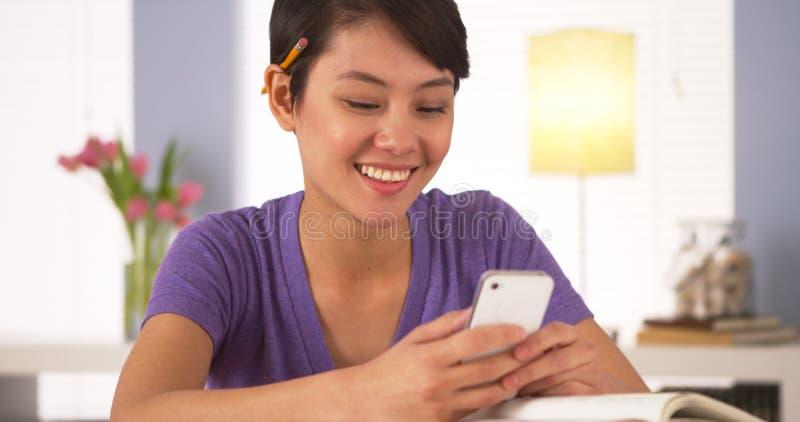 Smsande klasskompis för kinesisk kvinna på smartphonen royaltyfri foto