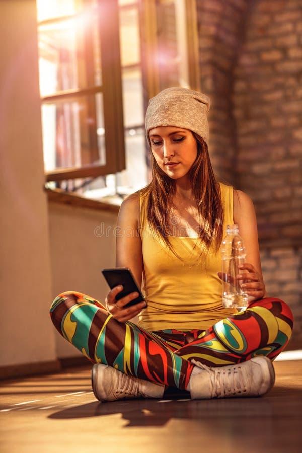 Smsande messaging för stads- smartphone för flicka hållande royaltyfria bilder