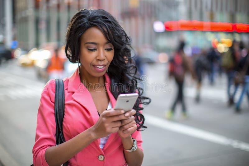 Smsande mobiltelefon för svart afrikansk amerikankvinna i stad arkivbilder