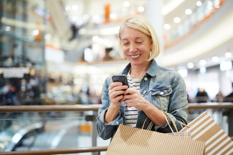 Smsande sms för lycklig kvinna i shoppinggalleria royaltyfria bilder