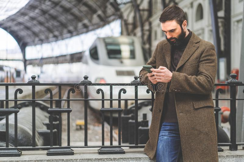 Smsande smsmeddelande för skäggig affärsman på hans mobiltelefon Tillfällig yrkesmässig entreprenör som använder smartphonen på k royaltyfri fotografi