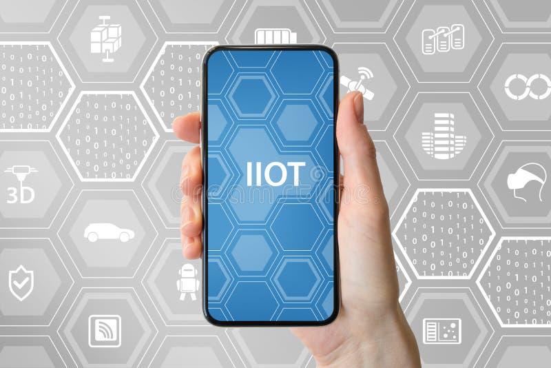 Smsar den industriella internet för IIOT av saker visat på skärmen av den moderna frameless smartphonen holdingen för bakgrundsgr royaltyfri foto