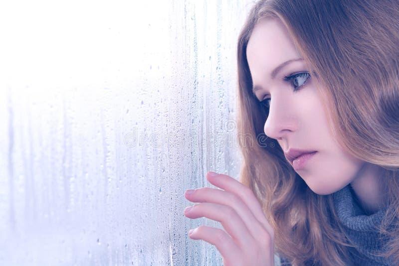 Smucenie dziewczyna przy okno w deszczu zdjęcia royalty free