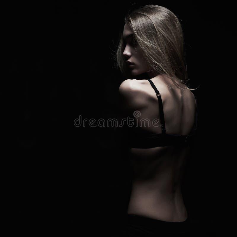 Smucenie młoda kobieta z nagim plecy nad czarnym tłem zdjęcie royalty free