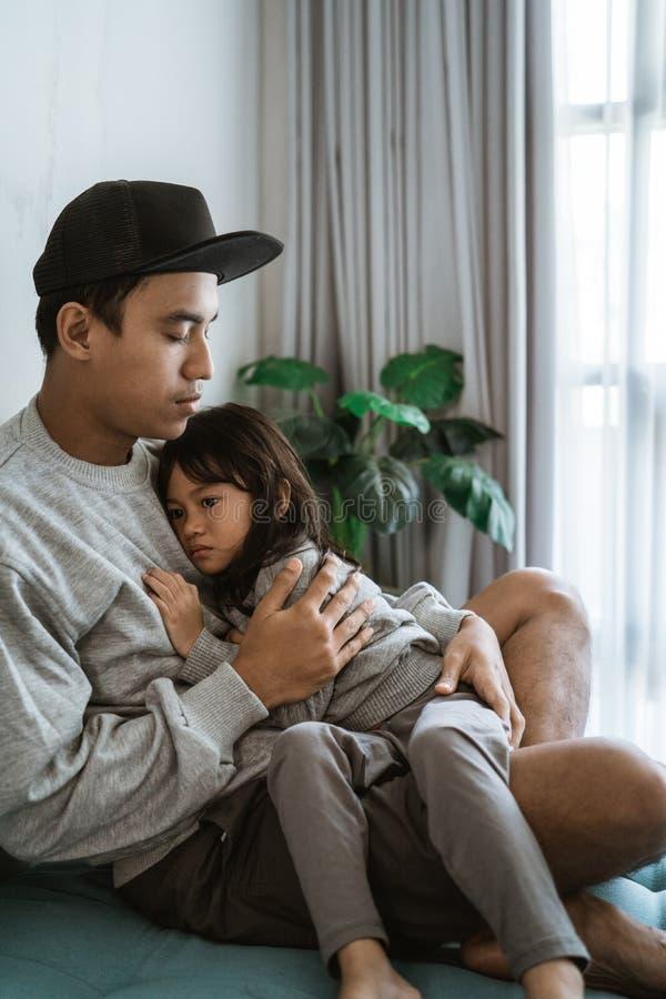 Smucenie mała dziewczynka obejmujący ojciec gdy siedzący zdjęcie royalty free