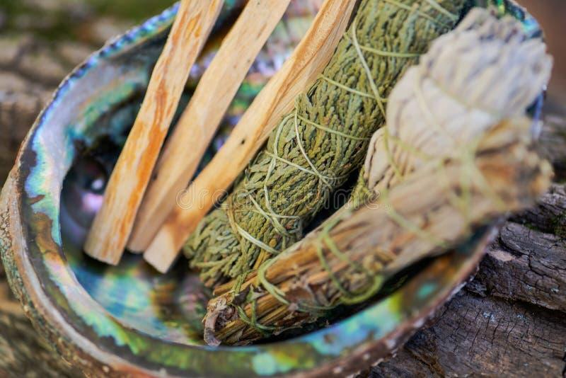 Smudge uitrusting - Palo Santo-stokken, droge witte wijze Salvia apiana van Wildcrafted, vulgaris Bijvoetalsem, en de Ceder van S stock fotografie