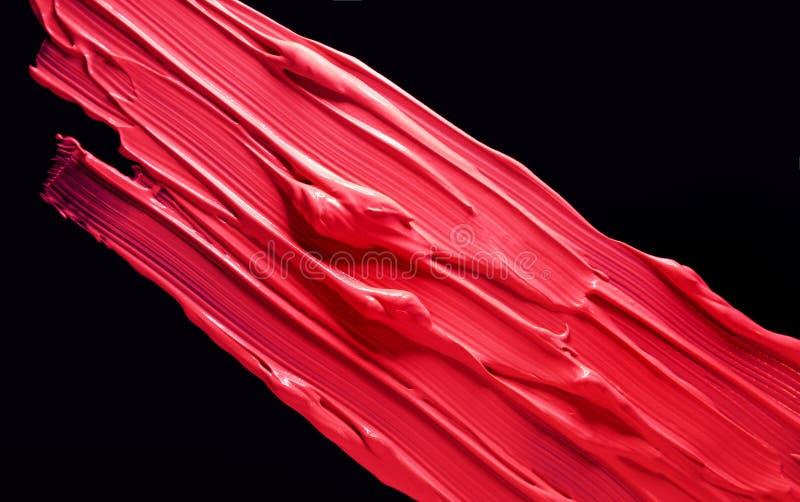 Smudged red burgundy dark lipstick isolated on black background stock photo