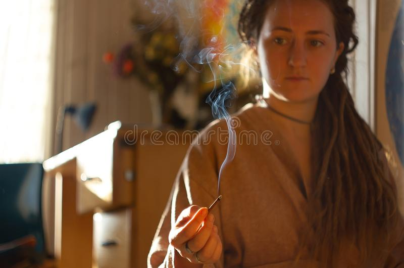 Smudging ceremony using Peruvian Palo Santo holy wood incense stick. At interior home stock photo