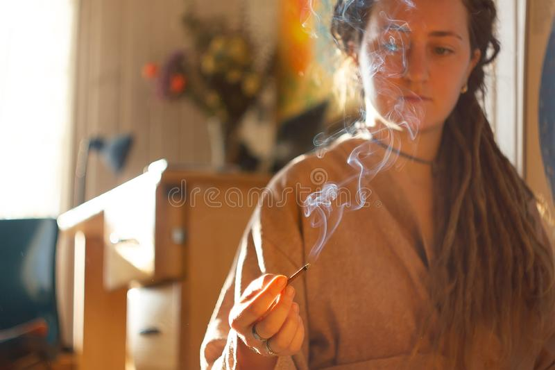 Smudging ceremony using Peruvian Palo Santo holy wood incense stick. At interior home royalty free stock images