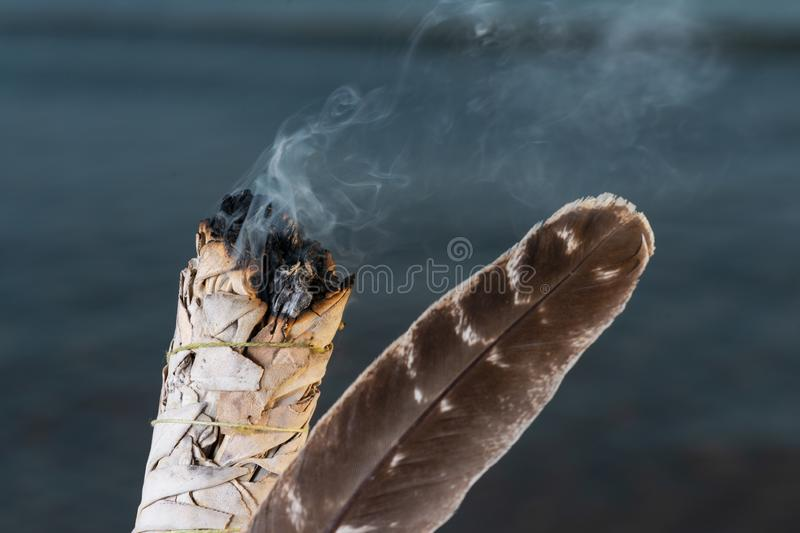 Smudging Ritual using burning thick leafy bundle of White Sage Grade A barred Turkey Smudging Feather on the beach at sunrise royalty free stock photos