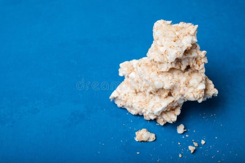 Smulor och haveri av frasiga mellanmål för diet-ris på en blå bakgrund, tomt utrymme för text royaltyfri bild