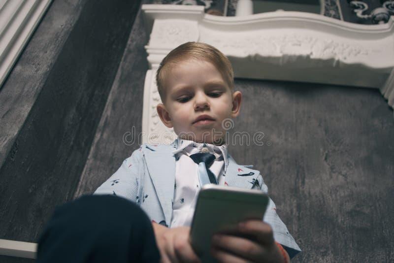 Smutna chłopiec Patrzeje telefon komórkowego Z zdjęcia stock