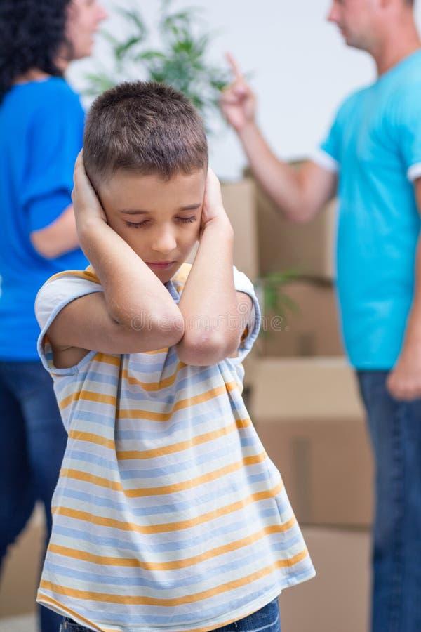 Smutna chłopiec w nowym domu podczas gdy rodziców kłócić się zdjęcia stock