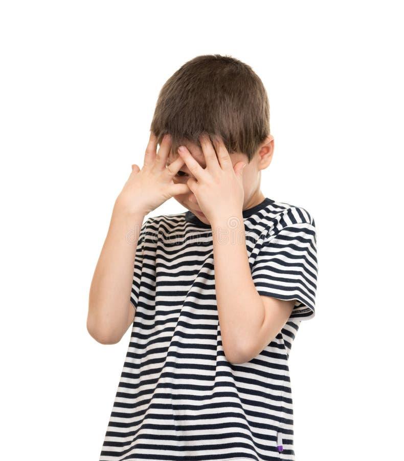 Smutna chłopiec zakrywa jego twarzy ręki obraz stock