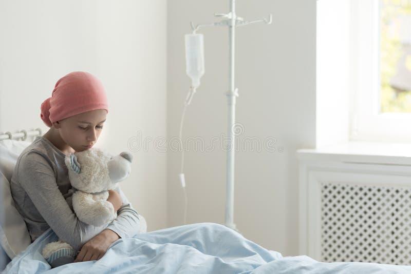 Smutna chora nastolatek dziewczyna siedzi samotnie w hospicjumu łóżku, trzymający misia, czekać na jej lekarkę zdjęcia royalty free