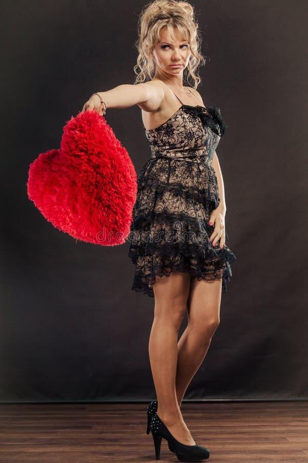 Smutna dojrzała kobieta trzyma czerwonego serce na czerni obraz stock