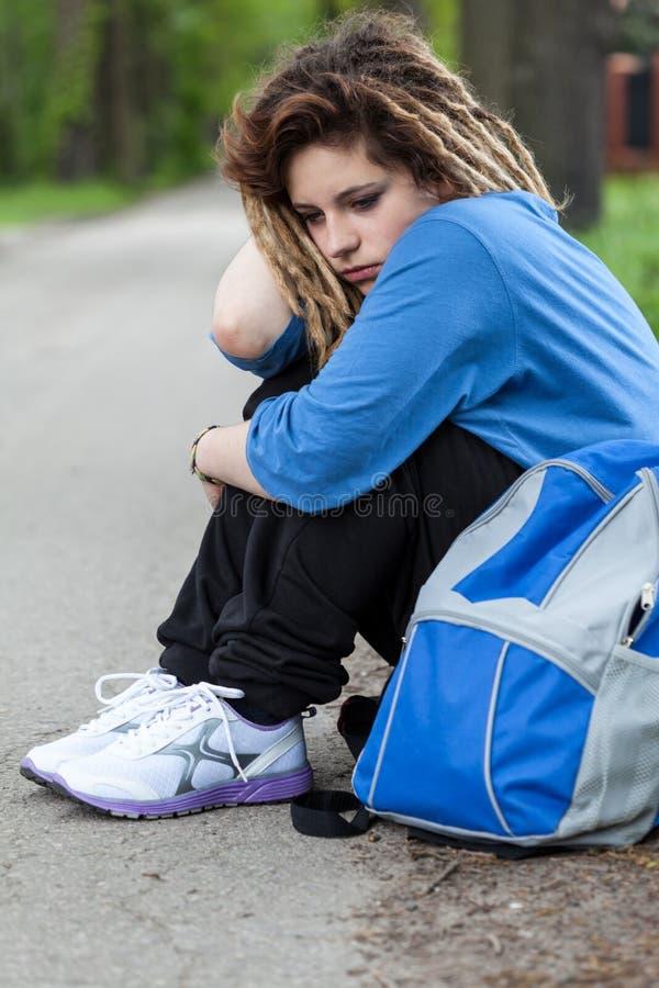 Smutna dziewczyna siedzi na drodze z dreadlocks zdjęcia royalty free