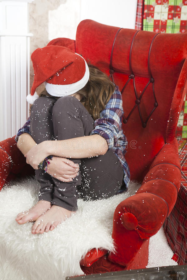 Smutna dziewczyna w szkockiej kraty koszula i nakrętce Święty Mikołaj obsiadanie na krześle Święty Mikołaj no przynosił prezentów obrazy royalty free
