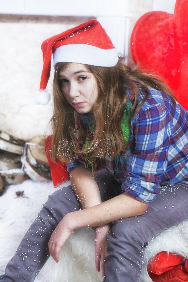 Smutna dziewczyna w szkockiej kraty koszula i nakrętce Święty Mikołaj obsiadanie na krześle Święty Mikołaj no przynosił prezentów zdjęcia royalty free