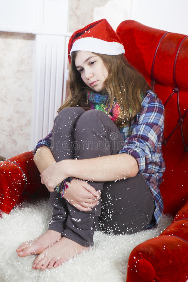 Smutna dziewczyna w szkockiej kraty koszula nakrętce Święty Mikołaj obsiadanie na krześle i Święty Mikołaj no przynosił prezentów obraz stock
