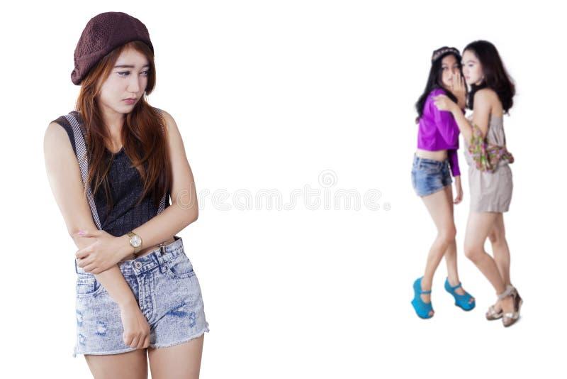 Smutna dziewczyna z przyjaciółmi plotkuje na plecy zdjęcie royalty free