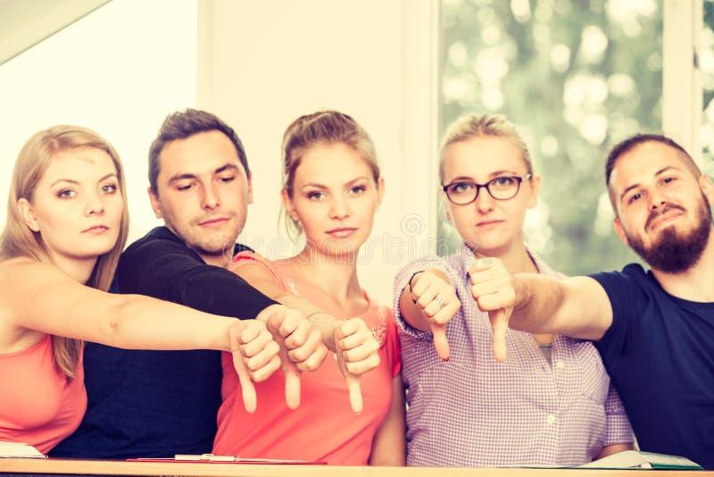 Smutna grupa ucznie daje kciukom zestrzela obraz stock