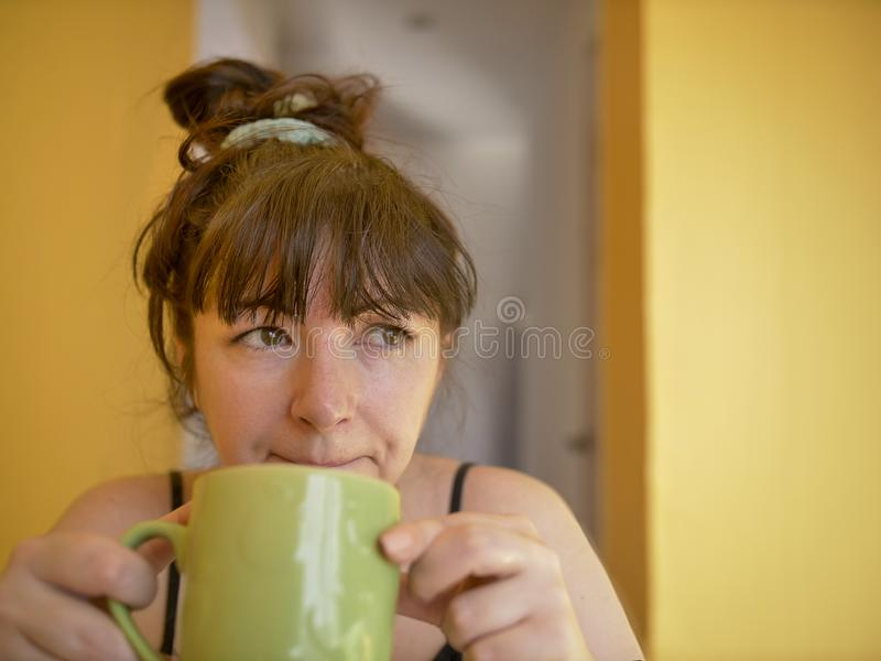 Smutna i śpiąca młoda kobieta z filiżanka kawy w ranku w domu zdjęcie stock