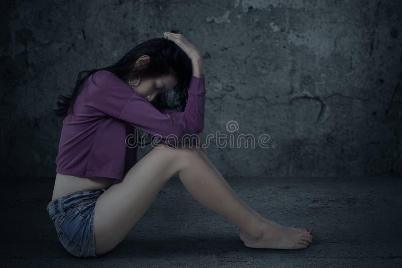 Smutna i zaakcentowana dziewczyna siedzi samotnie zdjęcie royalty free