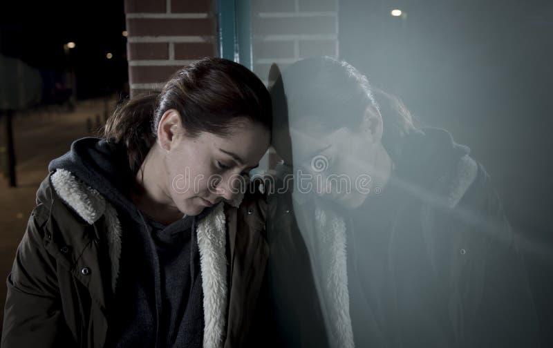 Smutna kobieta samotnie opiera na ulicznym okno przy nocy cierpienia depresji płaczem w bólu obrazy stock
