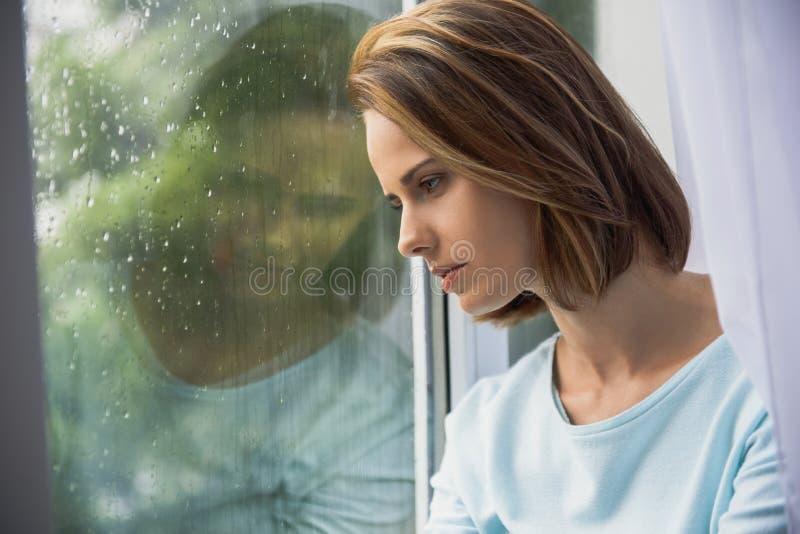 Smutna kobieta siedzi indoors podczas gdy padający zdjęcia stock