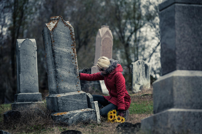 Smutna kobieta w Opłakiwać Dotyka kocham one Gravestone fotografia royalty free