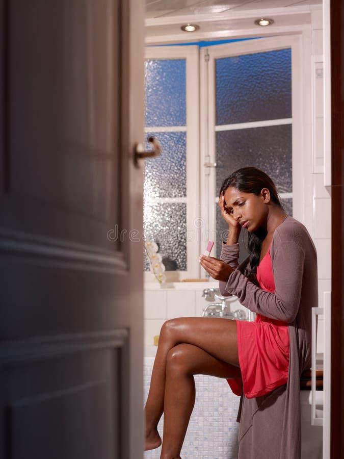Smutna kobieta z ciążowego testa zestawem zdjęcia royalty free