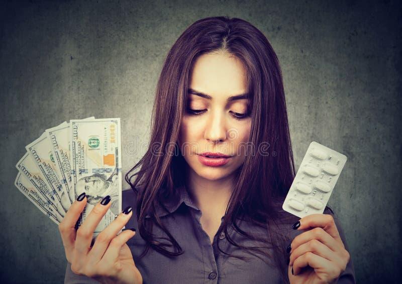 Smutna kobieta z pigułkami i pieniądze fotografia royalty free