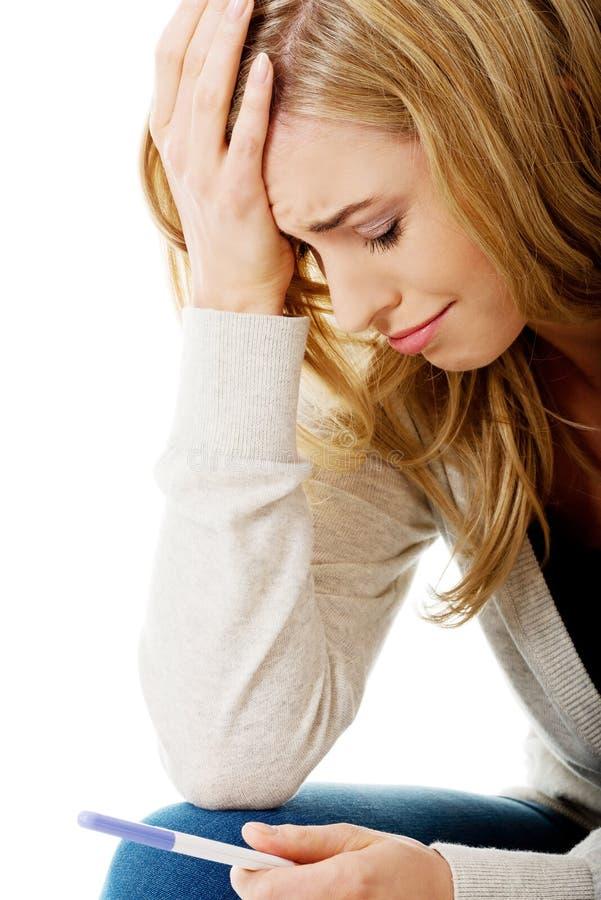 Smutna młoda kobieta trzyma ciążowego test fotografia stock