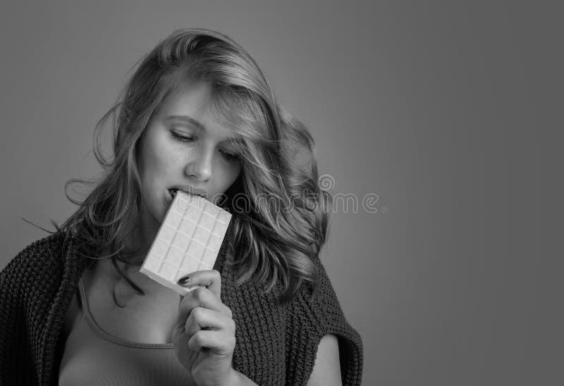 Smutna młoda piękna kobieta je białą czekoladę zdjęcia royalty free