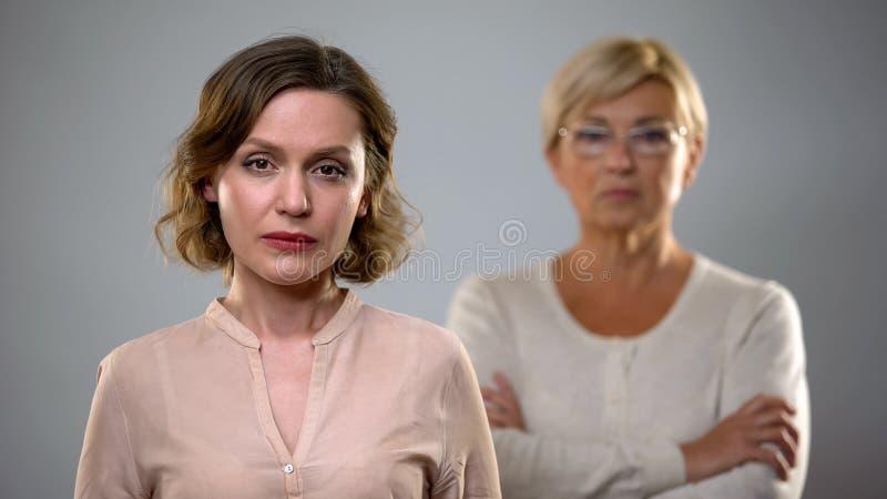 Smutna m?oda kobieta patrzeje in camera, surowa senior matki pozycja za, problem fotografia stock