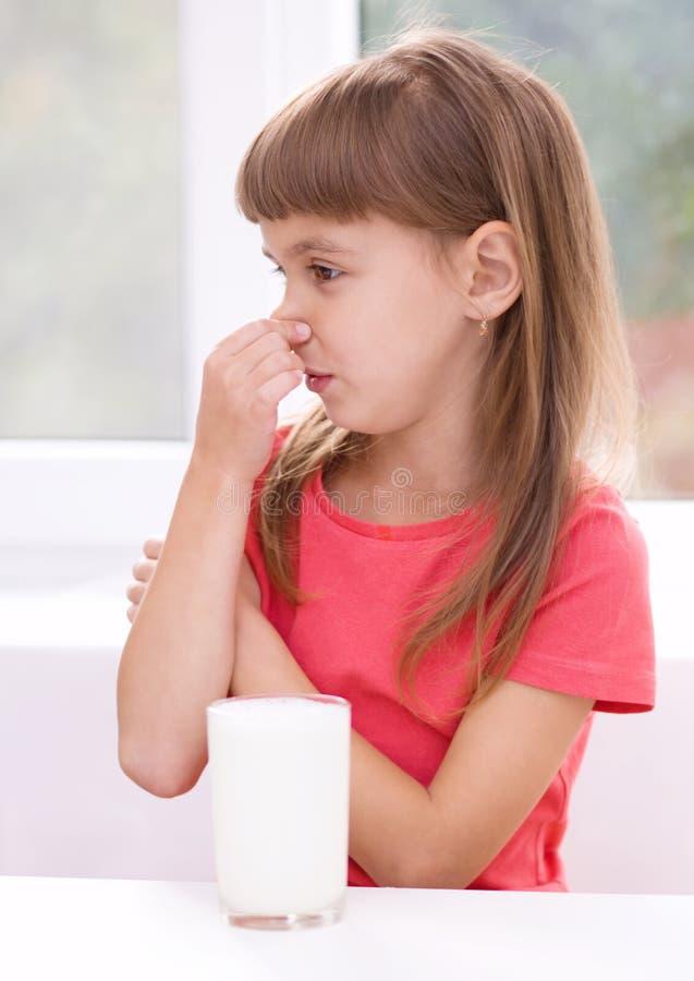 Smutna mała dziewczynka z szkłem mleko fotografia royalty free