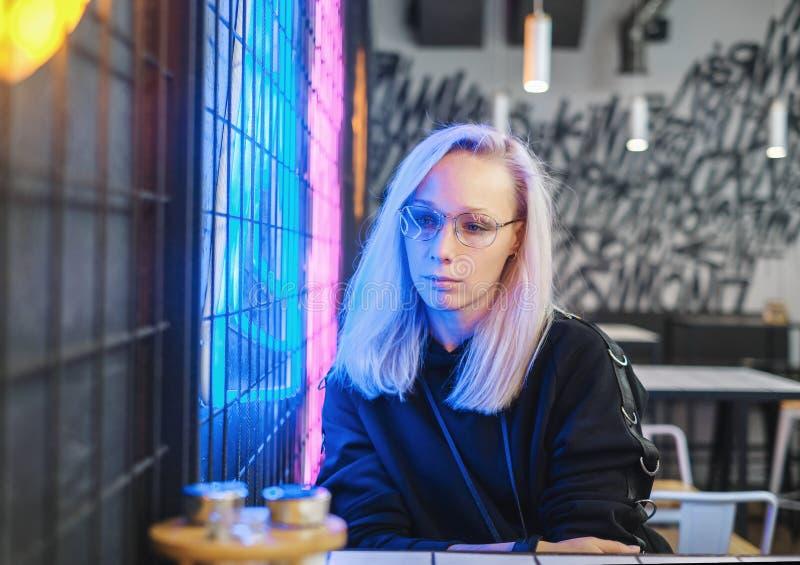 Smutna modniś blondynki dziewczyna siedzi w barze blisko neonowego w szkłach zdjęcia stock