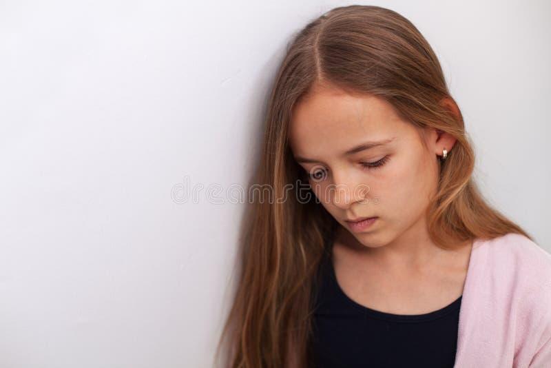 Smutna nastolatek dziewczyny pozycja białą ścianą z spuszczonymi oczami obrazy royalty free