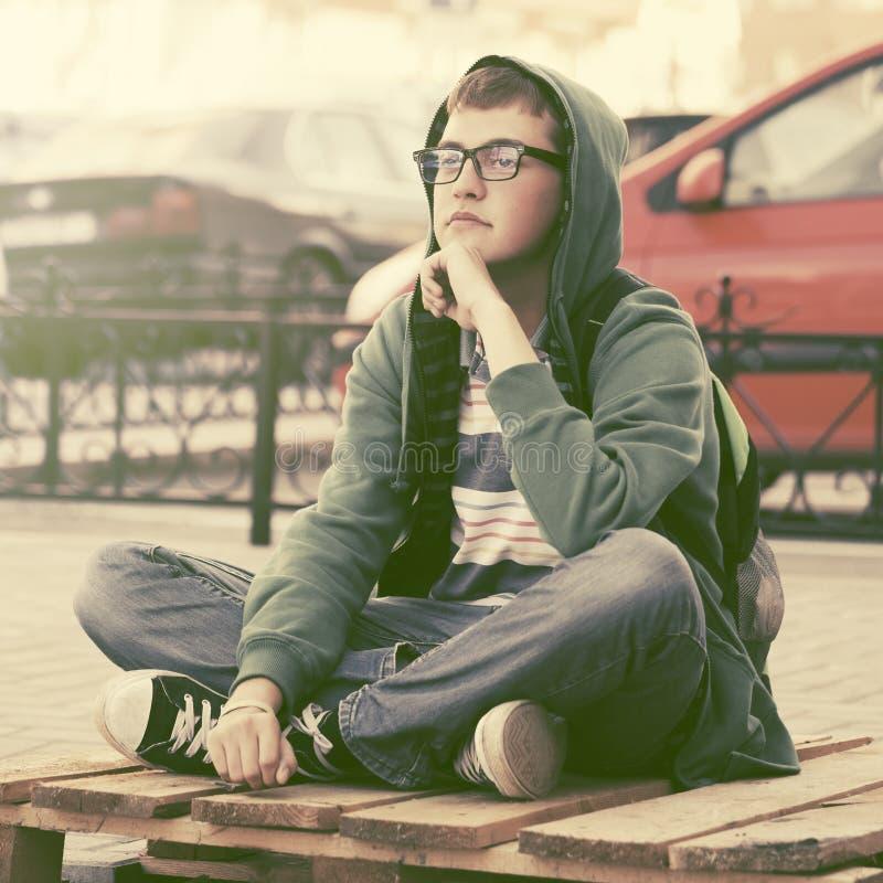 Smutna nastoletnia chłopiec w depresji obsiadaniu na chodniczku w miasto ulicie fotografia stock