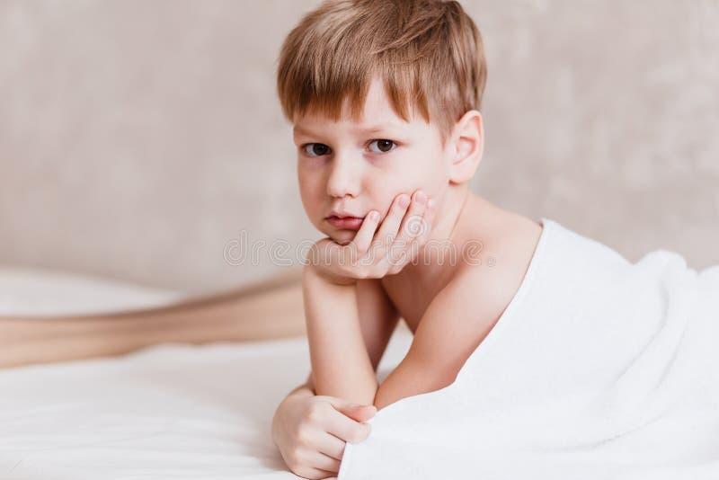 Smutna pięcioletnia stara Kaukaska chłopiec zakrywająca z białym Terry ręcznikiem w sypialni po kąpać się zdjęcie stock