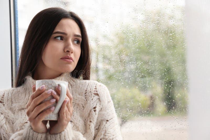 Smutna piękna kobieta z filiżanką blisko okno na deszczowym dniu zdjęcie stock