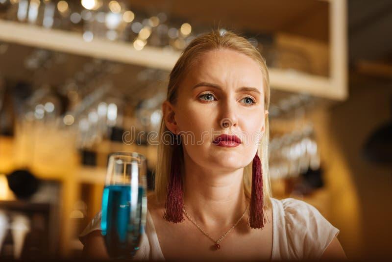 Smutna ponura młoda kobieta pije alkohol samotnie obraz royalty free