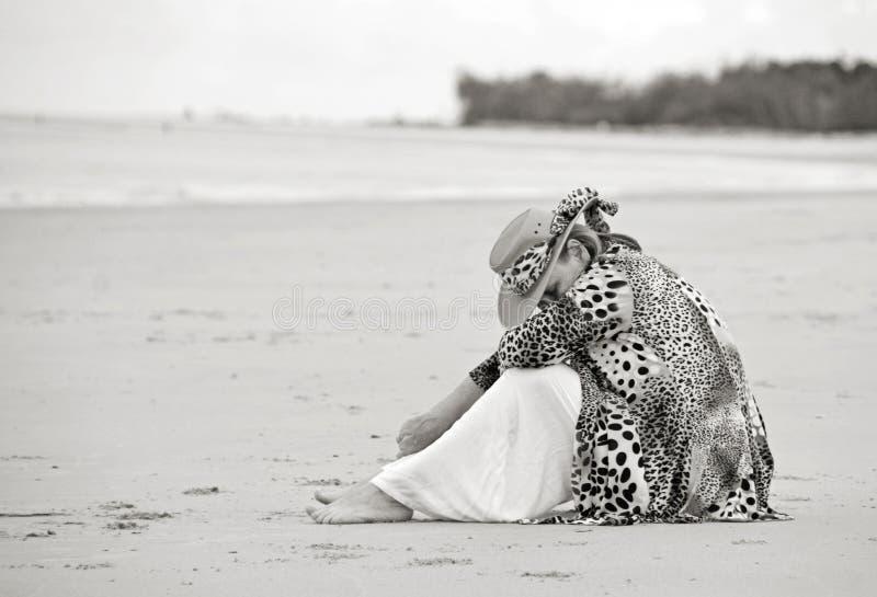 Smutna przygnębiona rozpacza kobieta siedzi samotnie na pustej plaży obraz royalty free